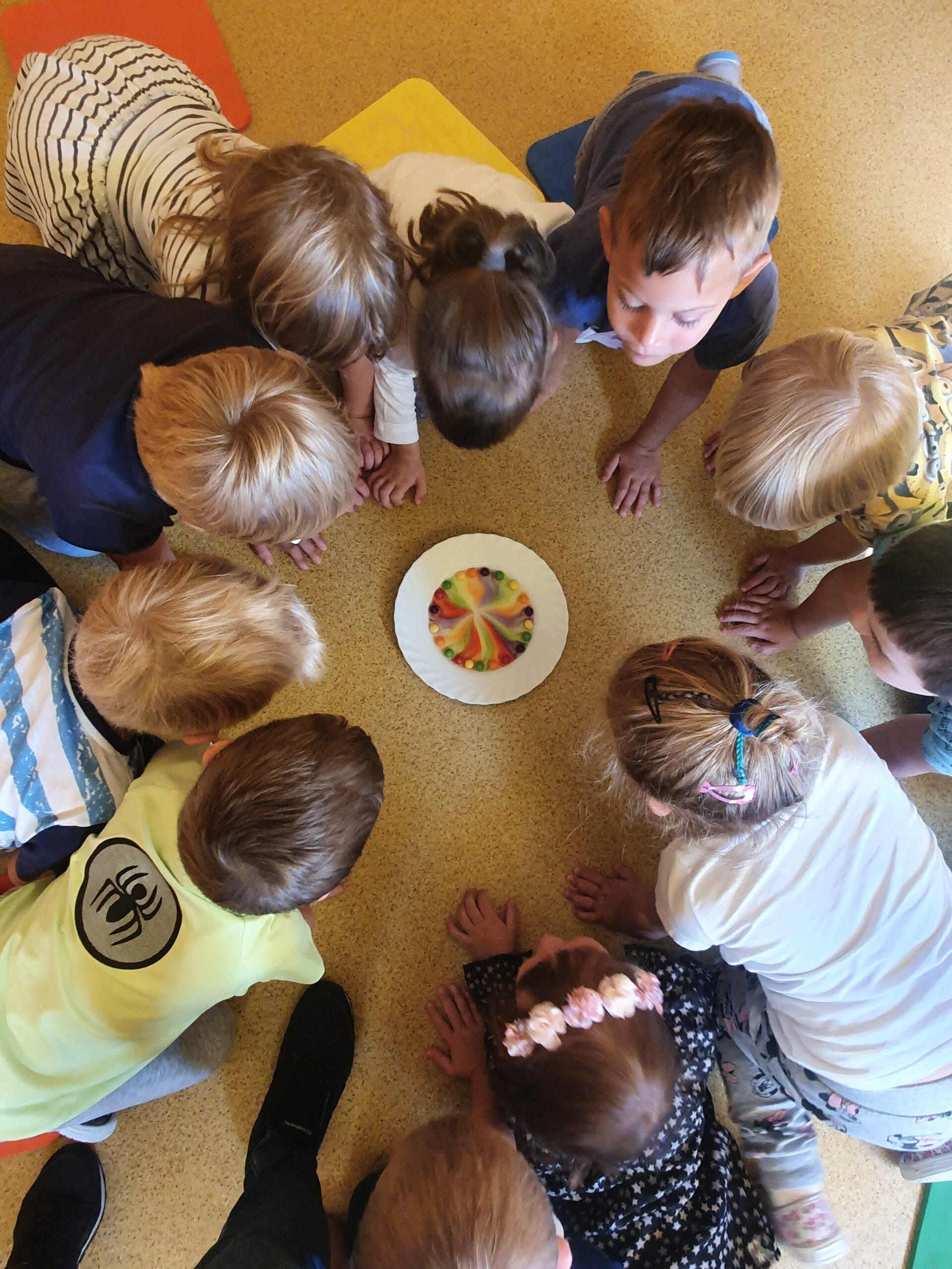 dzieci nachylają się nad talerzykiem na którym kolorowe cukierki rozpuszczają się w wodzie tworząc tęczę