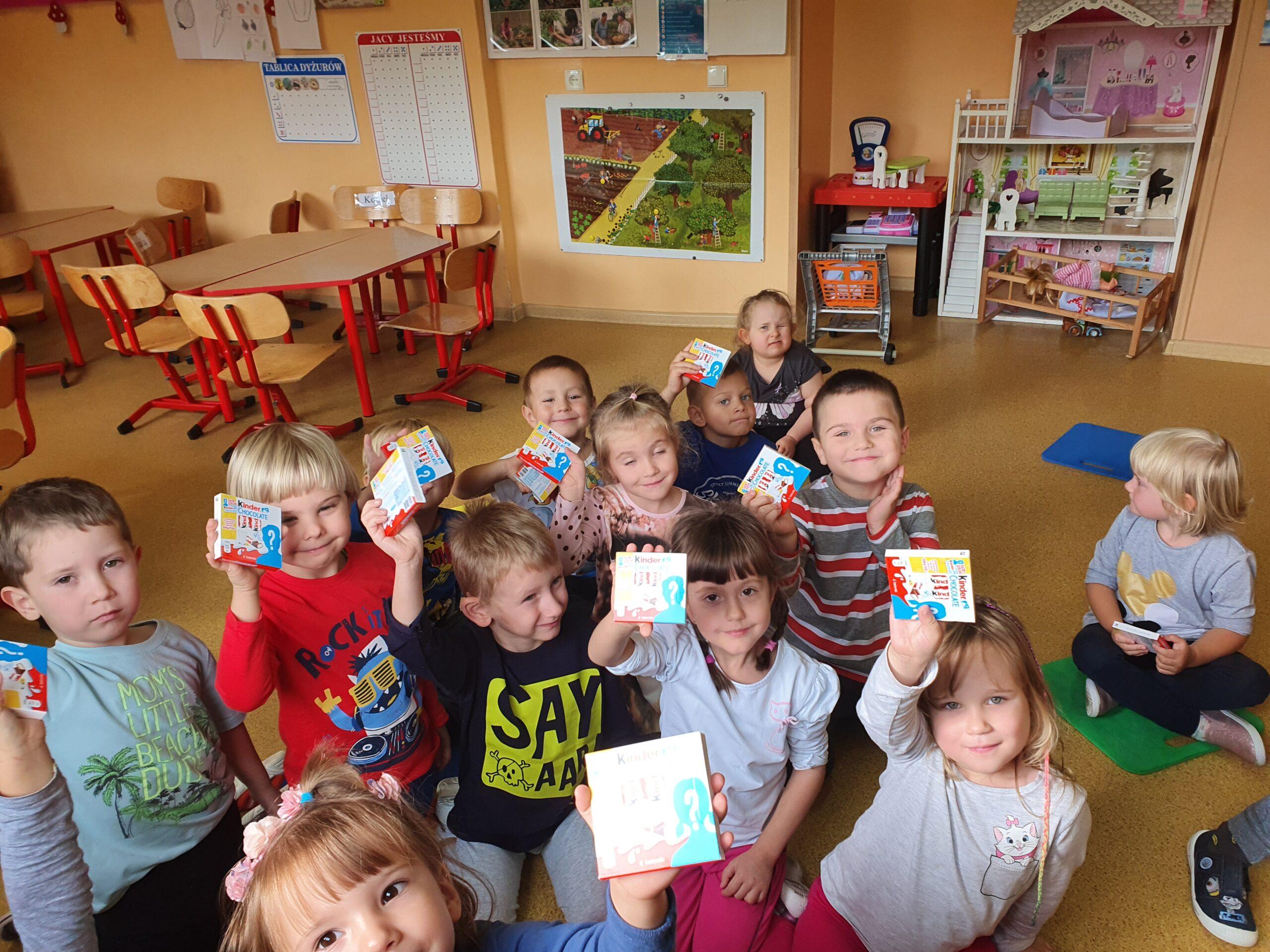 dzieci pozują do zdjęcia i pokazują otrzymane czekoladki