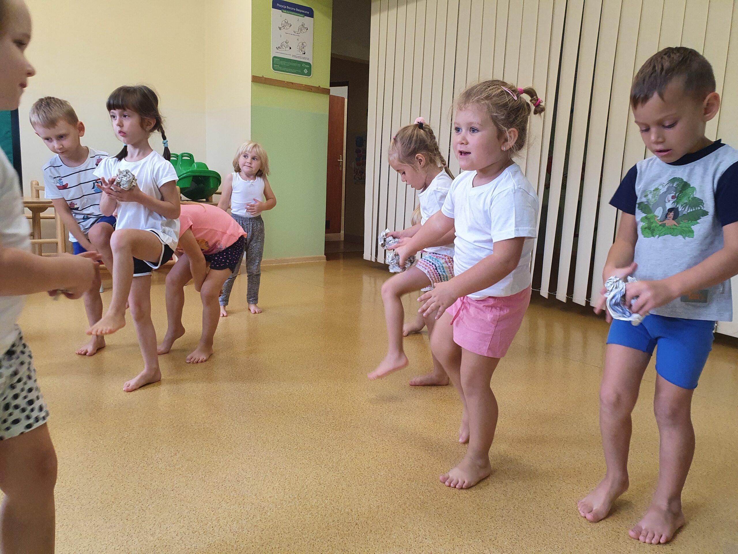 dzieci ćwiczą z kulkami z gazet, podnoszą nogi i przekładają pod nimi gazetę