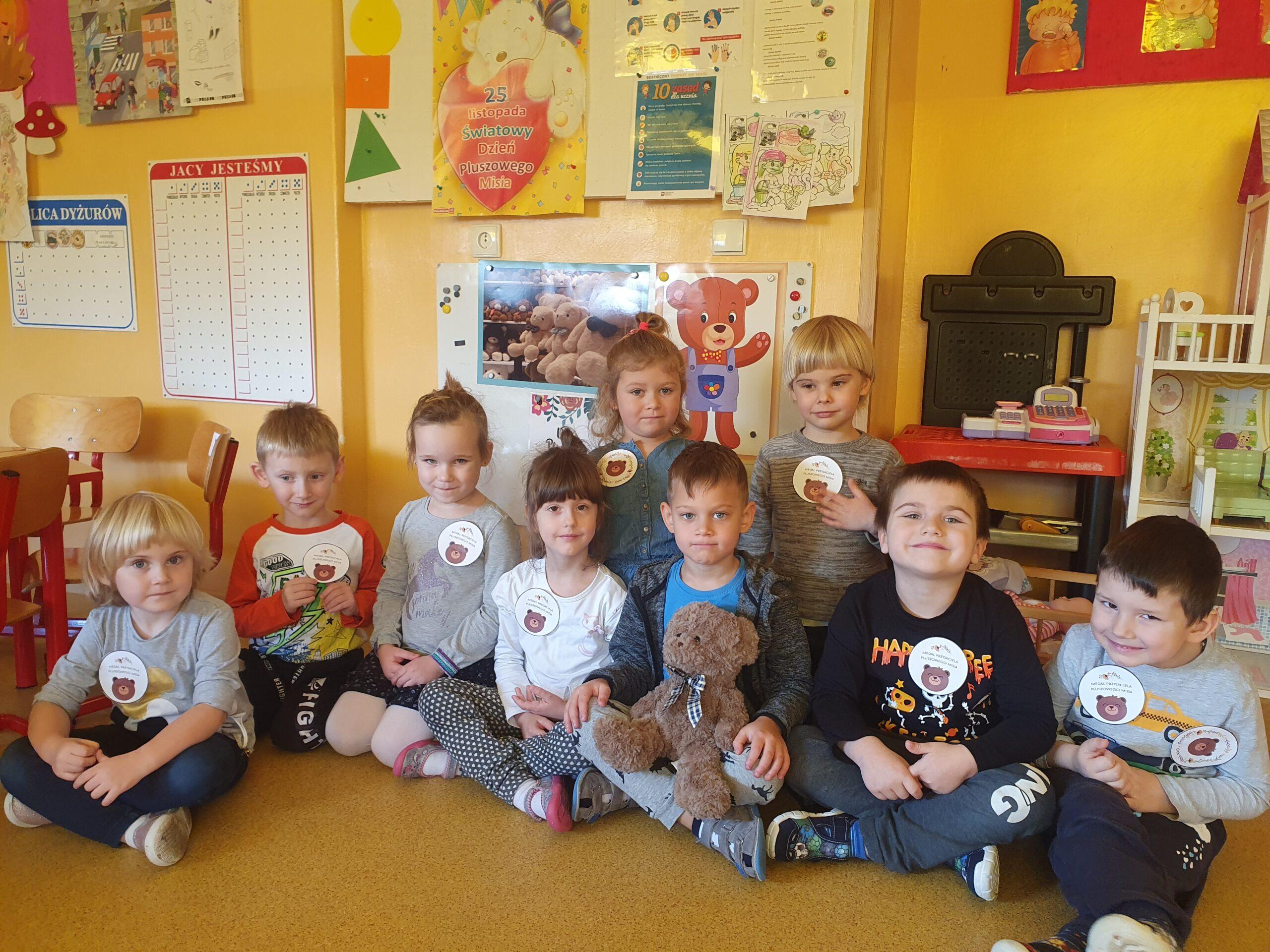 dzieci siedzą w siadzie skrzyżnym, maja przyczepione papierowe medale przyjaciela p-luszowego misia. Chłopczyk trzyma na kolanach pluszowego misia
