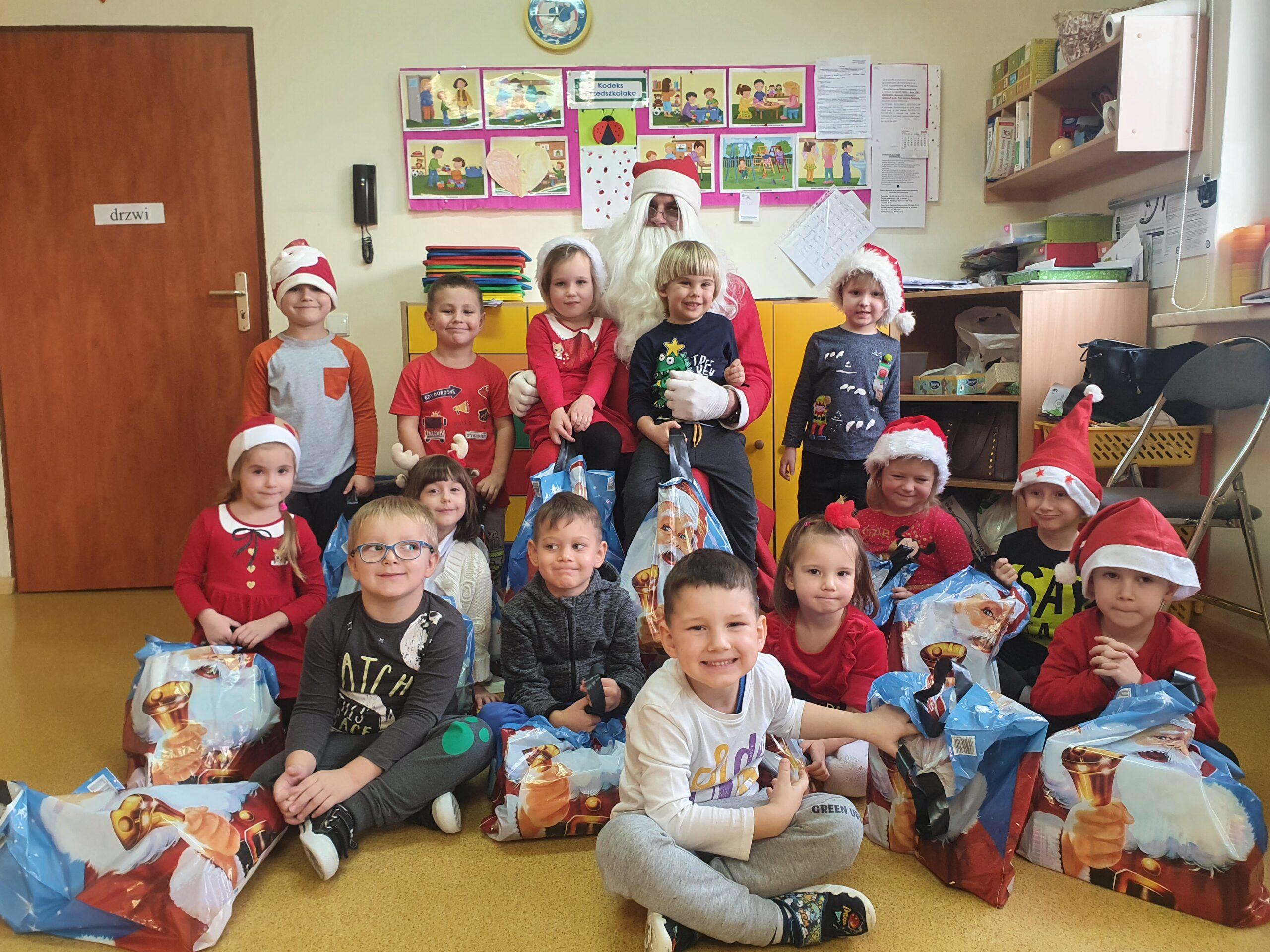 grupa dzieci siedzi i stoi przed Mikołajem, trzymają otrzymane przez niego prezenty, dwoje dzieci siedzi mikołajowi na kolanach