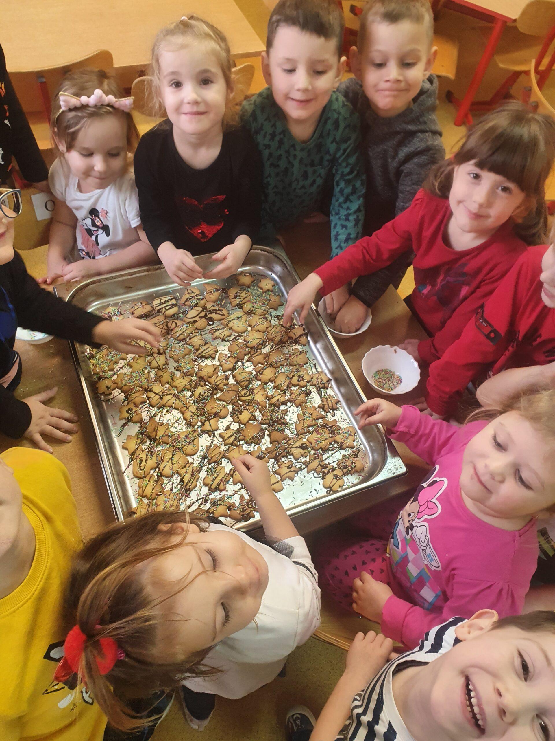 dzieci polewaja ciasteczka polewą i posypują kolorową posypką