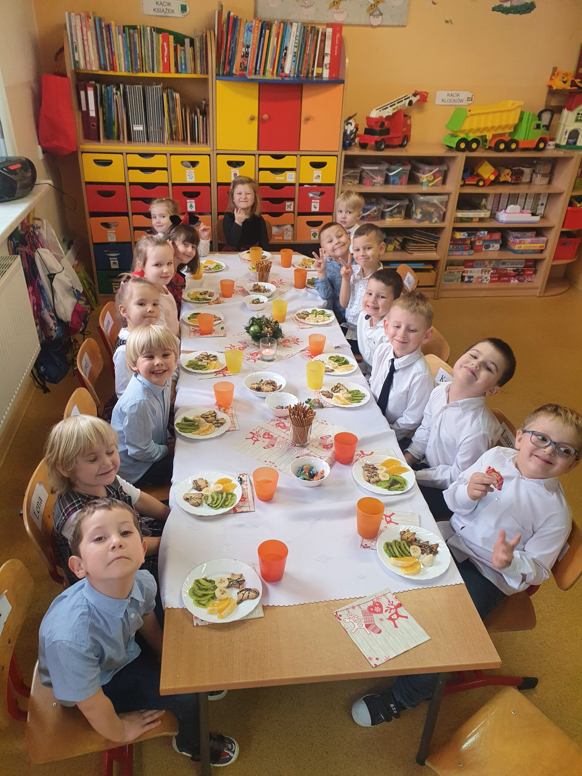 cała grupa dzieci siedzi przy stole, przy każdym dziecku stoi talerz z owocami, kubeczki z sokiem na środku stołu są paluszki i cukierki