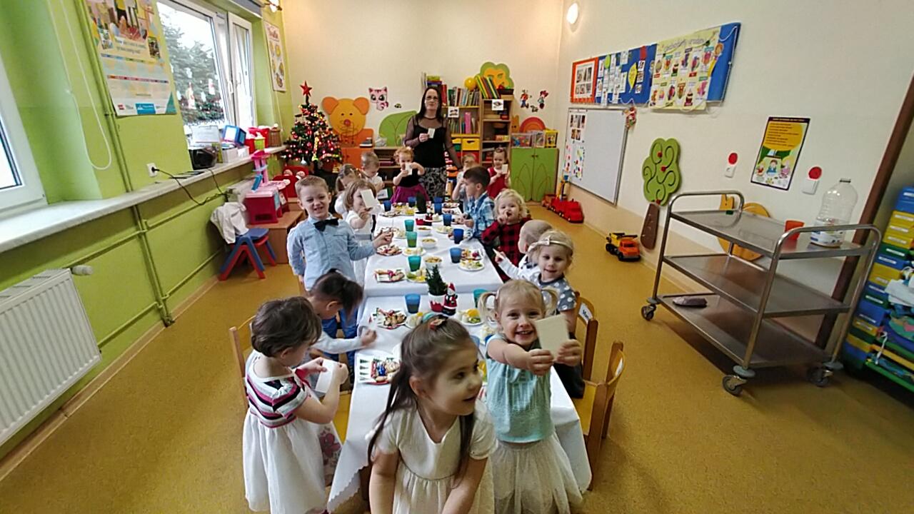 Dzieci odwracają się do Pani, która robi im zdjęcie. Dzieci się uśmiechają i pokazują opłatek.