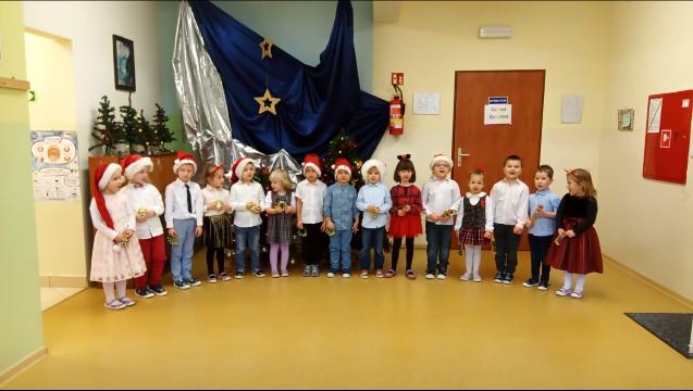 dzieci odświętnie ubrane stoją w rzędzie, niektóre maja na głowie czapki mikołajkowe. Dzieci recytują wiesz i śpiewają posenkę