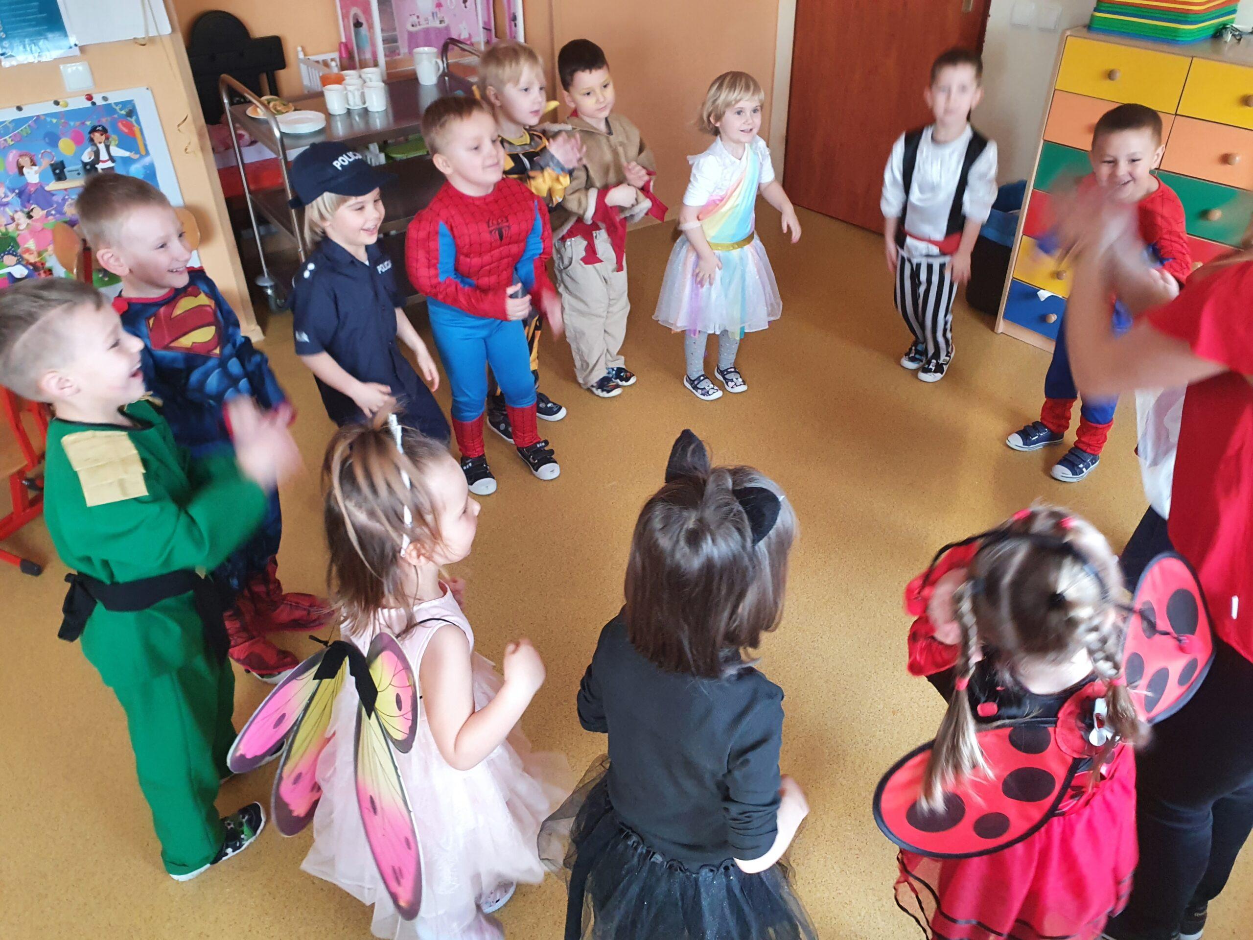 dzieci w strojach karnawałowych stoją w kółku z panią i naśladują ruchem tekst piosenki