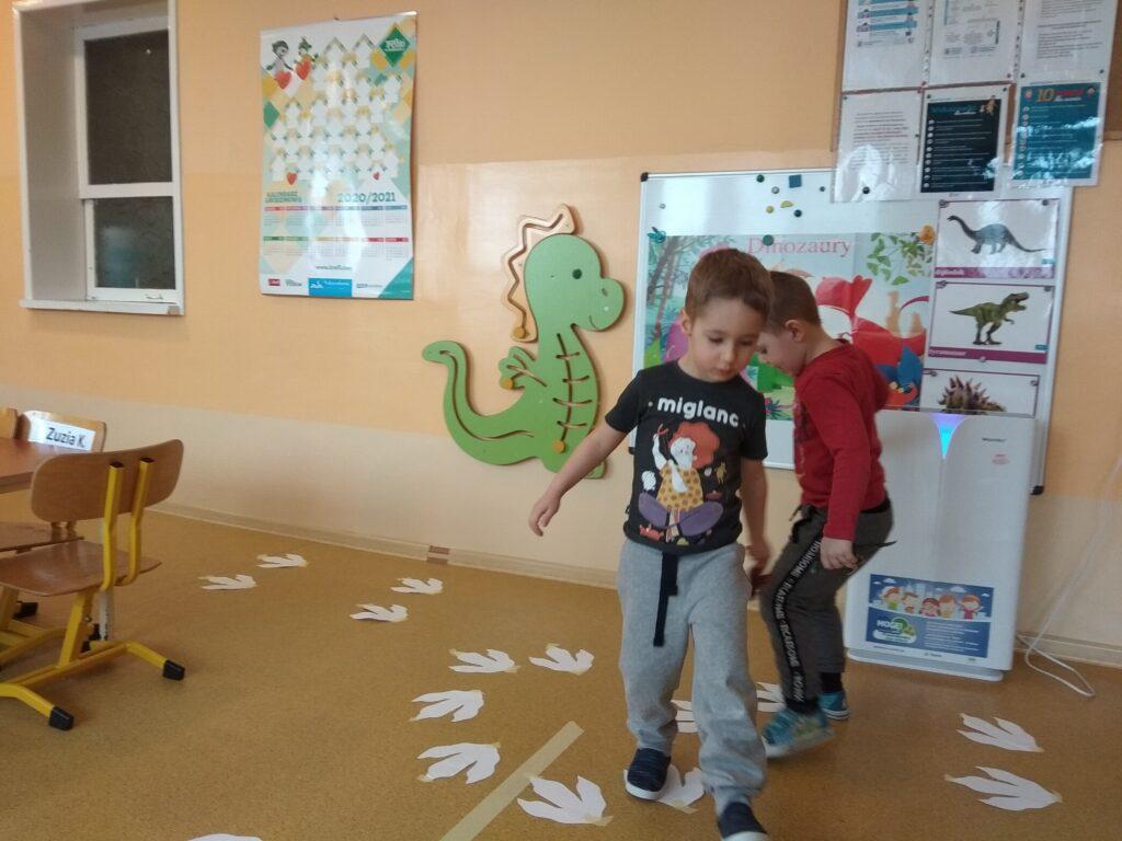 Chłopcy idą po papierowych śladach dinozaura.
