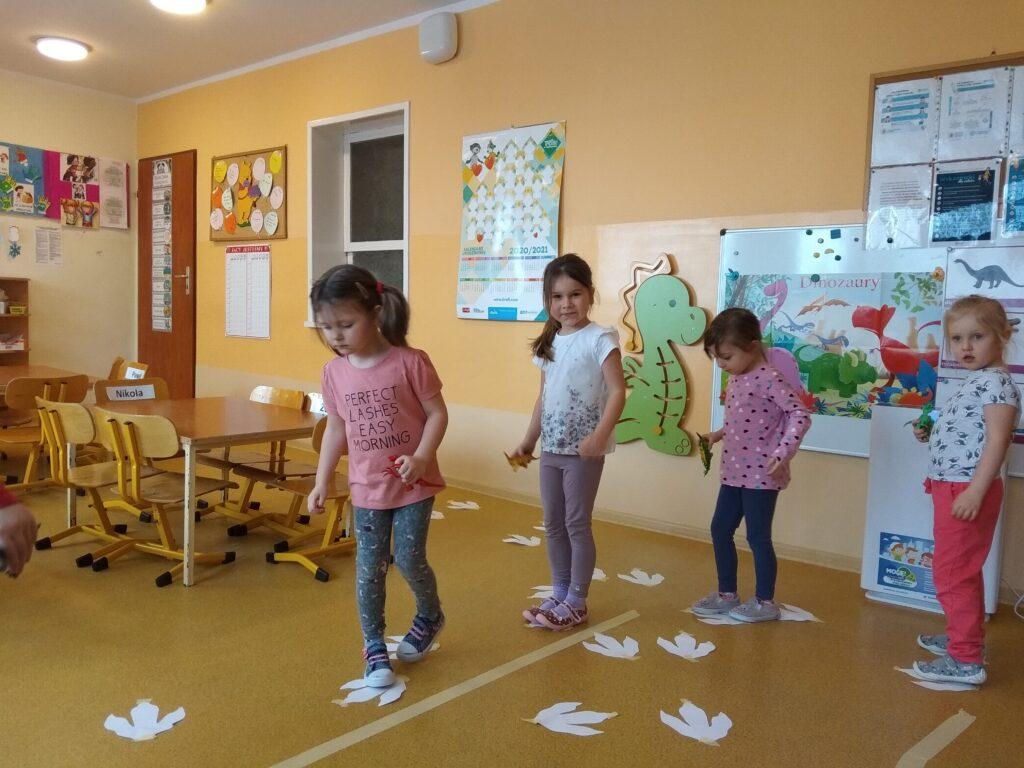 Dziewczynki idą jedna za drugą po papierowych śladach dinozaura.