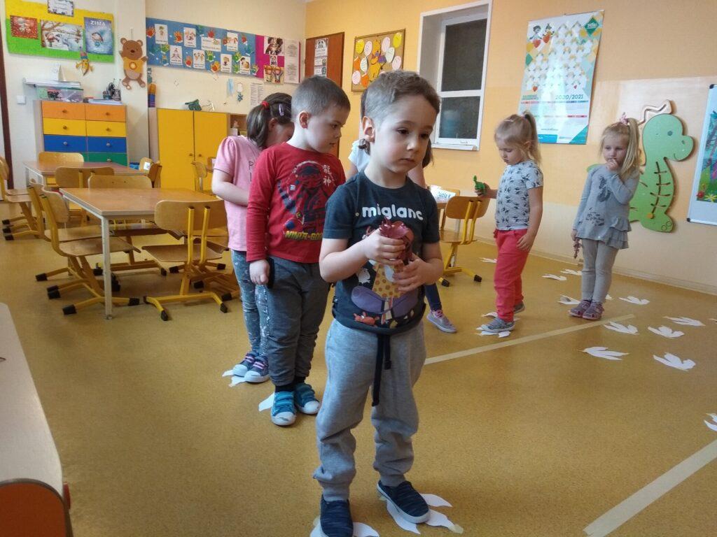 Dzieci stoją jeden za drugim na papierowych śladach stóp dinozaura.