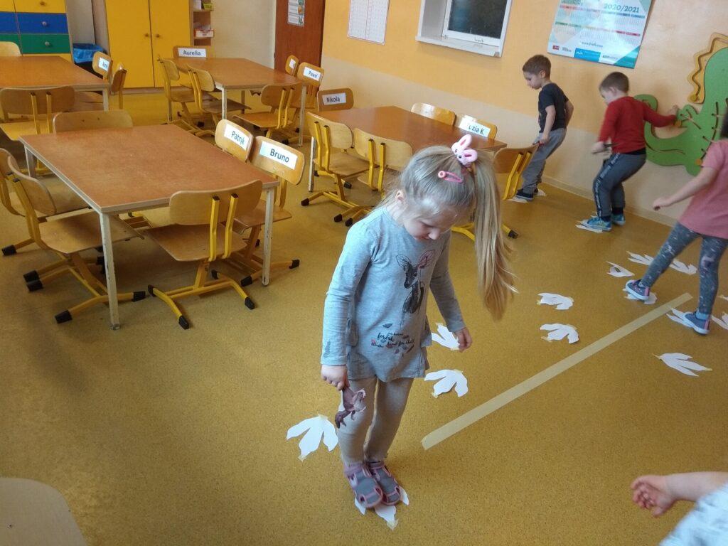Dzieci chodzą po papierowych śladach stóp dinozaura.