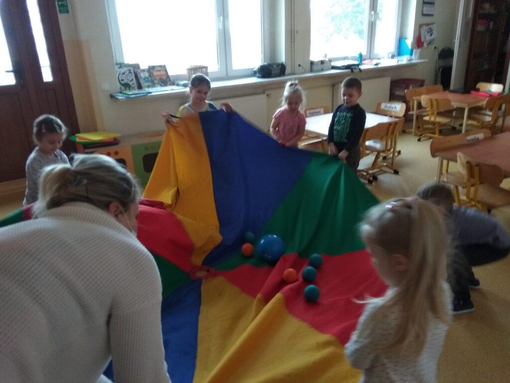 Dzieci trzymają chustę animacyjną, na której leżą kolrowe piłki.