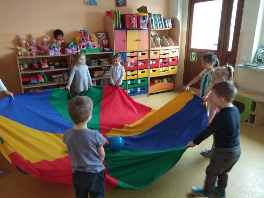 Dzieci stoją w kole i trzymają chustę animacyjną, na której leży niebieska piłka.