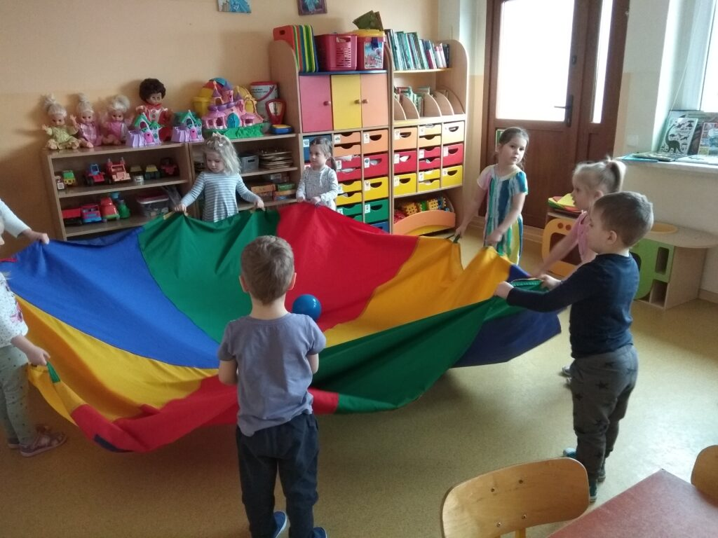 Dzieci bawią się chustą animacyjną na której leży niebieska piłka.