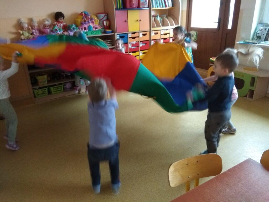 Dzieci bawią się chustą animacyjną. Dzieci machają chustą.