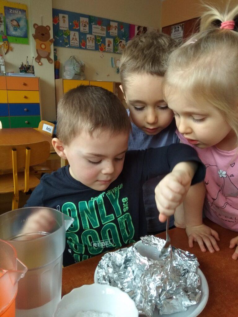 Chłopczyk wsypuje łyżeczką sodę do komina wulkanicznego. Obok stoi i się przygląda dziwewczynka i chłopczyk.