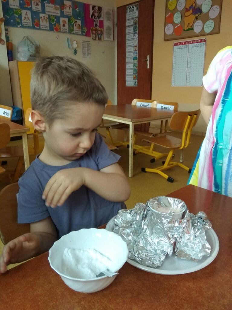 Chłopczyk sziedzi na krzesełku i obserwuje reakcję po wsypaniu sody do octu.
