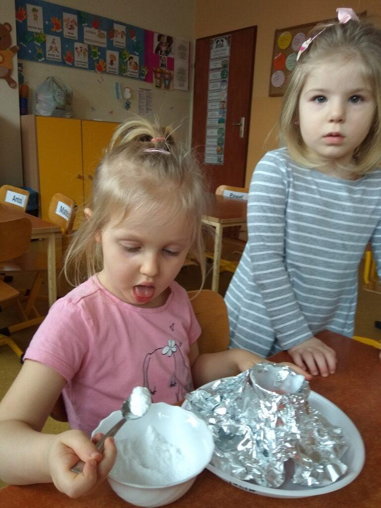 Dziewczynka nabiera łyżeczką sodę. Obok stoi druga dziewczynka.k
