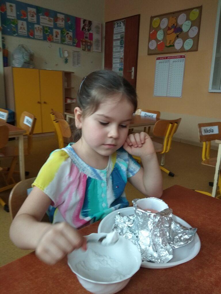 Dziewczynka nabiera na łyżeczkę sodę.