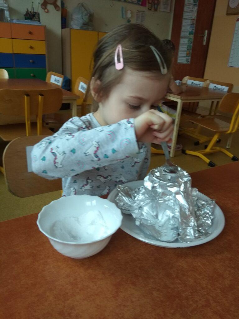 Dziewczynka wsypuje sodę do komina wulkanu