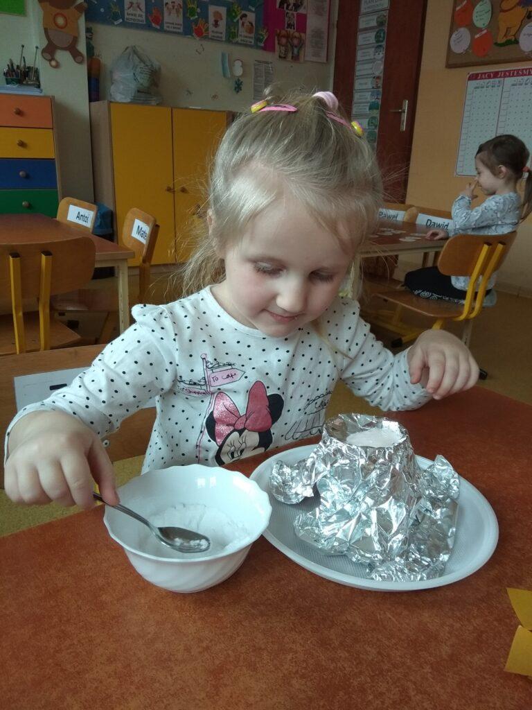 Dziewczynka nabiera łyżeczką sodę z miseczki
