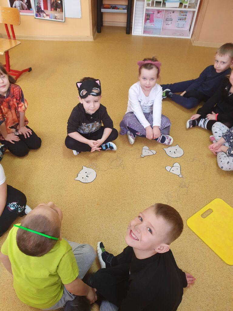 dzieci przebrane za kotki siedzą w kole na podłodze rozłożone są sylwety kotów i myszy potrzebne do gry zręcznościowej