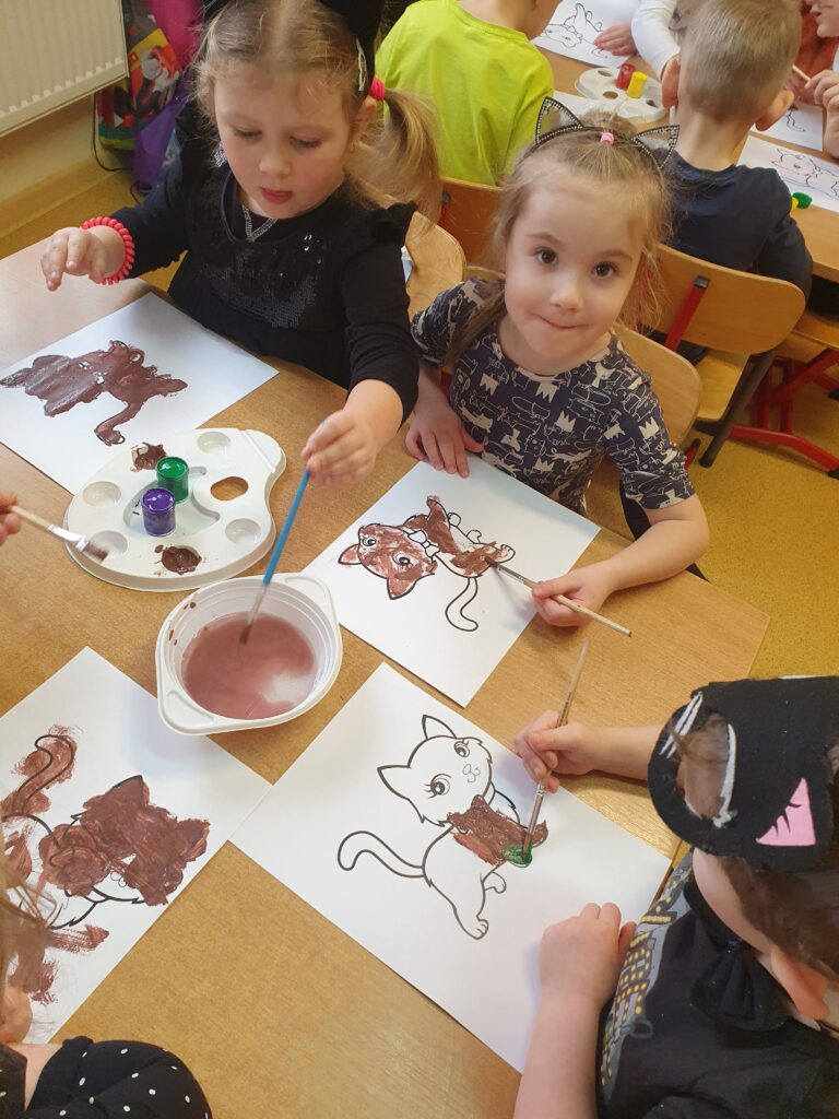 dzieci siedzą przy stoliku malują farbami sylwetę kota