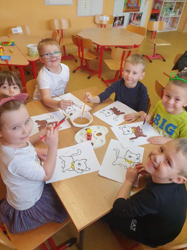 dzieci siedzą przy stoliku i malują farbami sylwetę kota