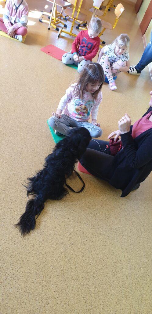 dziewczynka, pies i opiekun psa siedzą na podłodze