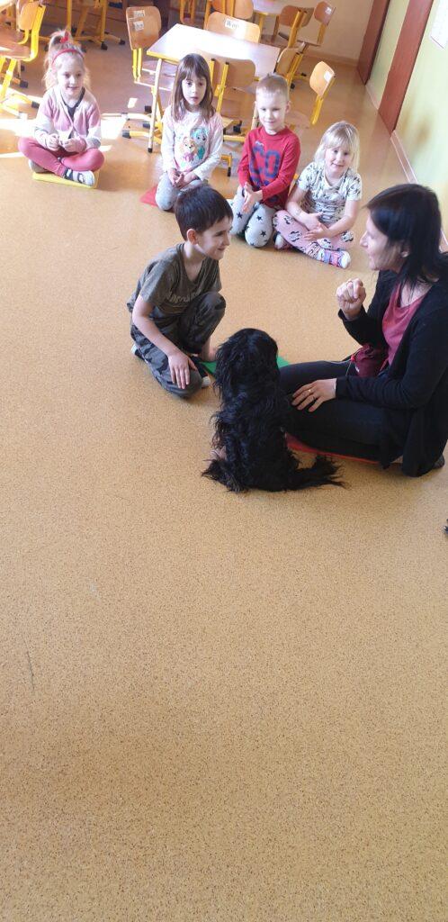 chłopczyk i pies w towarzystwie opiekuna psa siedzą na podłodze