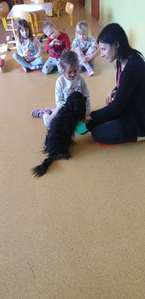 Dziewczynka karmi psa w towarzystwie opiekuna psa