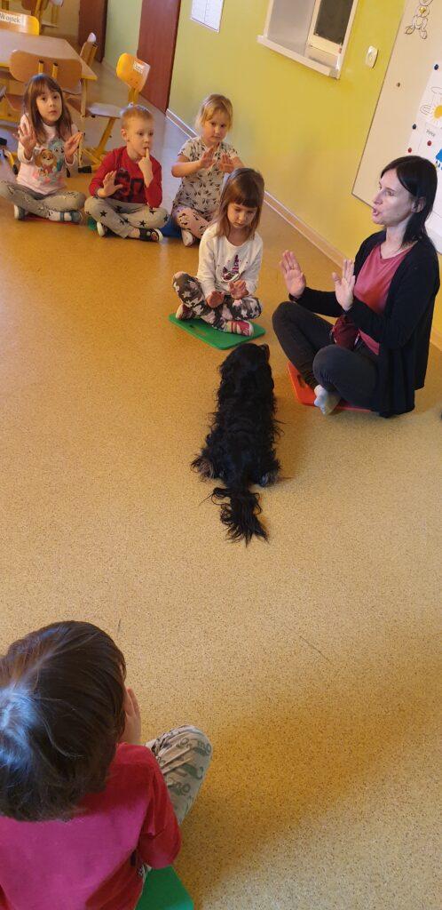 Opiekun psa mówi do dzieci, pies patrzy na opiekuna