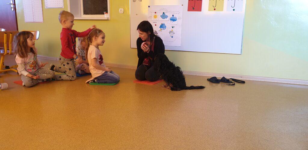 dziewczynka patrzy na Panią, pies siedzi