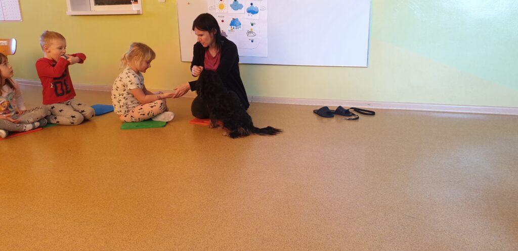 dziewczynka bierze smakołyk od opiekuna na rękę, piesi siedzi