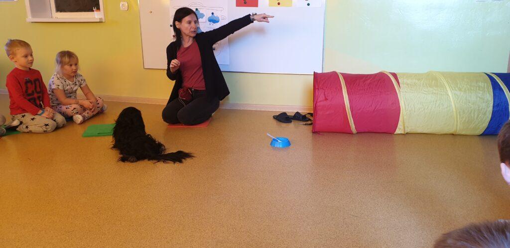 Opiekun psa wskazuje palcem zadanie do wykonania, pies siedzi i dzieci też