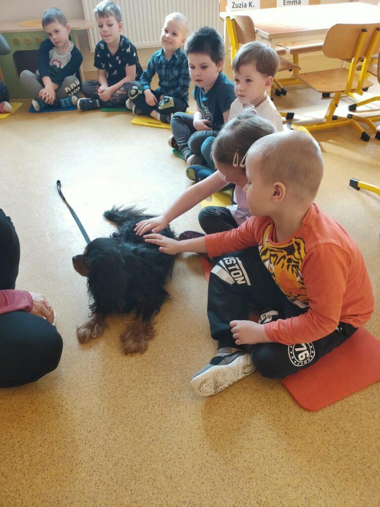 Dzieci siedzą na podłodze; wyciągają ręce i głaszczą psaą