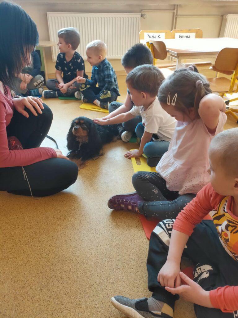 Dzieci siedzą na podlodze, obok siedzi pies, jest głaskany przez chłopca