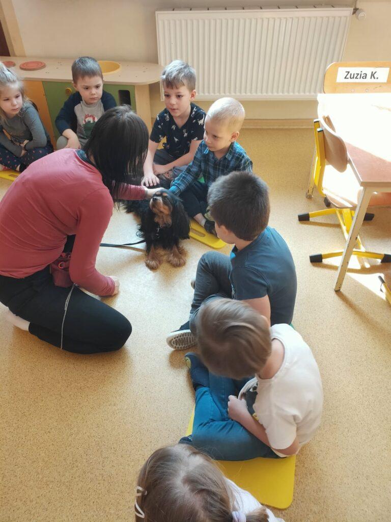 Chłopcy siedzą na podłodze, głaszczą psa. Obok siedzi właścicielka psa