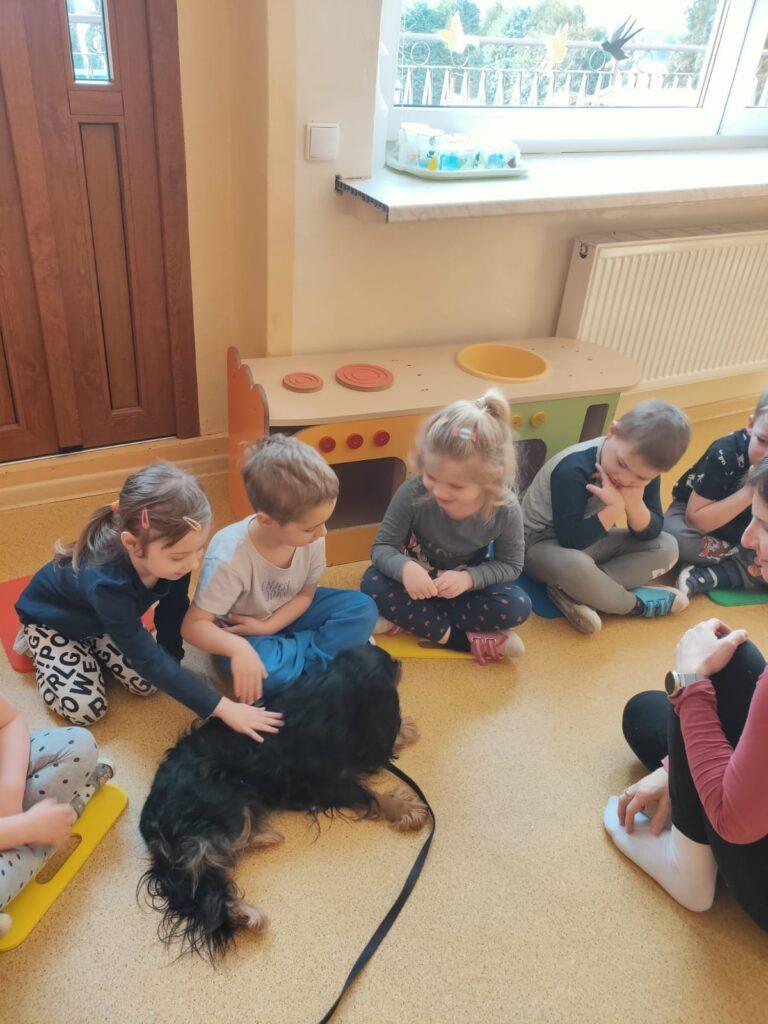 Dzieci siedzą na podłodze, pochylają się i głaszczą psa