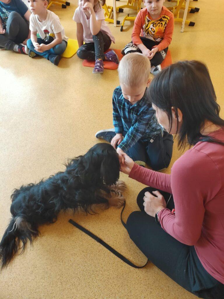 Pani siedzi na podlodze i chłopc wyciąga rękę aby nakarmić psa nakarmić psa