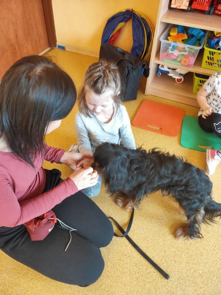 Pani i dziewczynka siedzą na podłodze i karmią psa