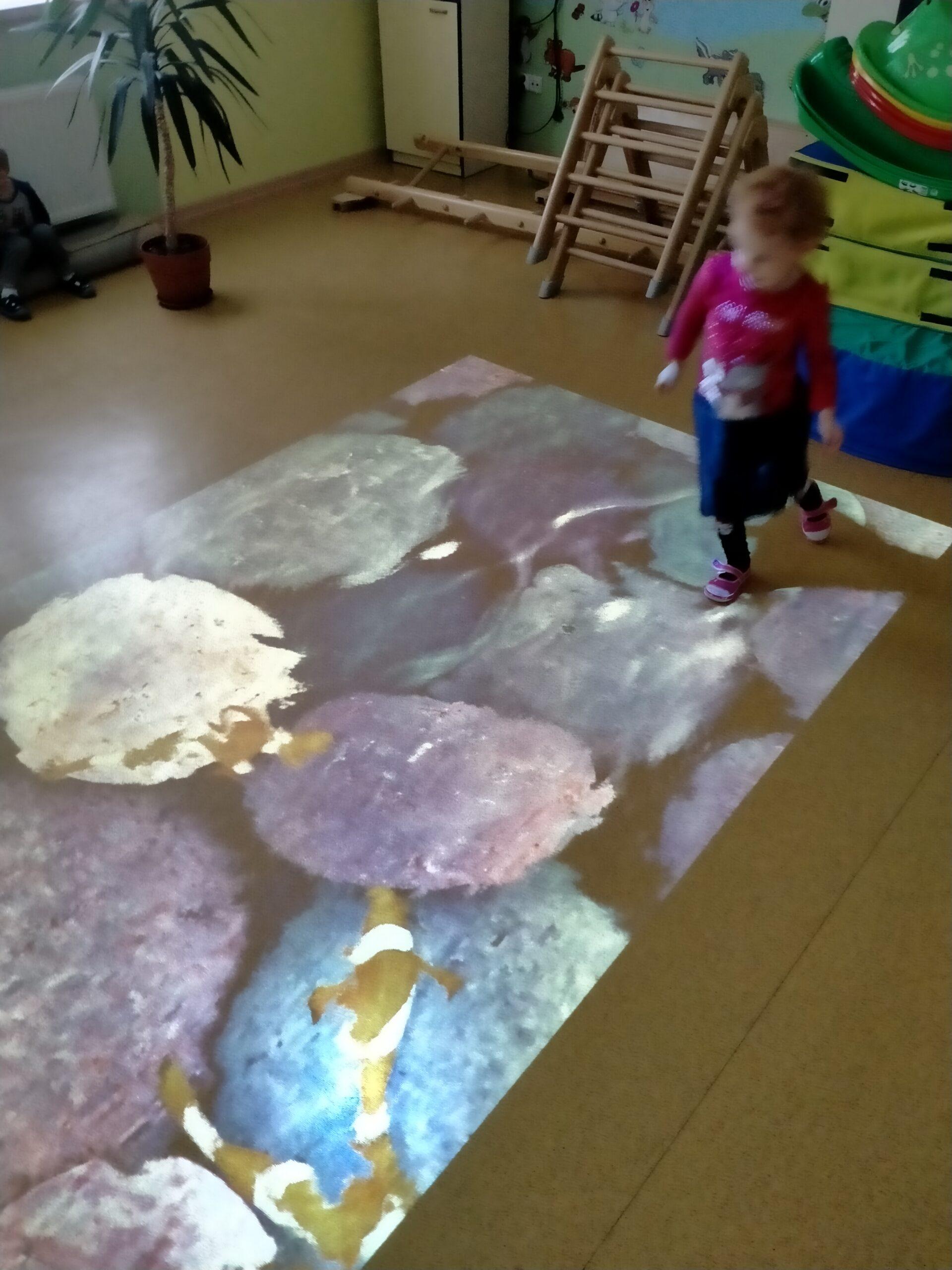 Dziewczynka stoi na multimedialnym dywanie i goni rybki.