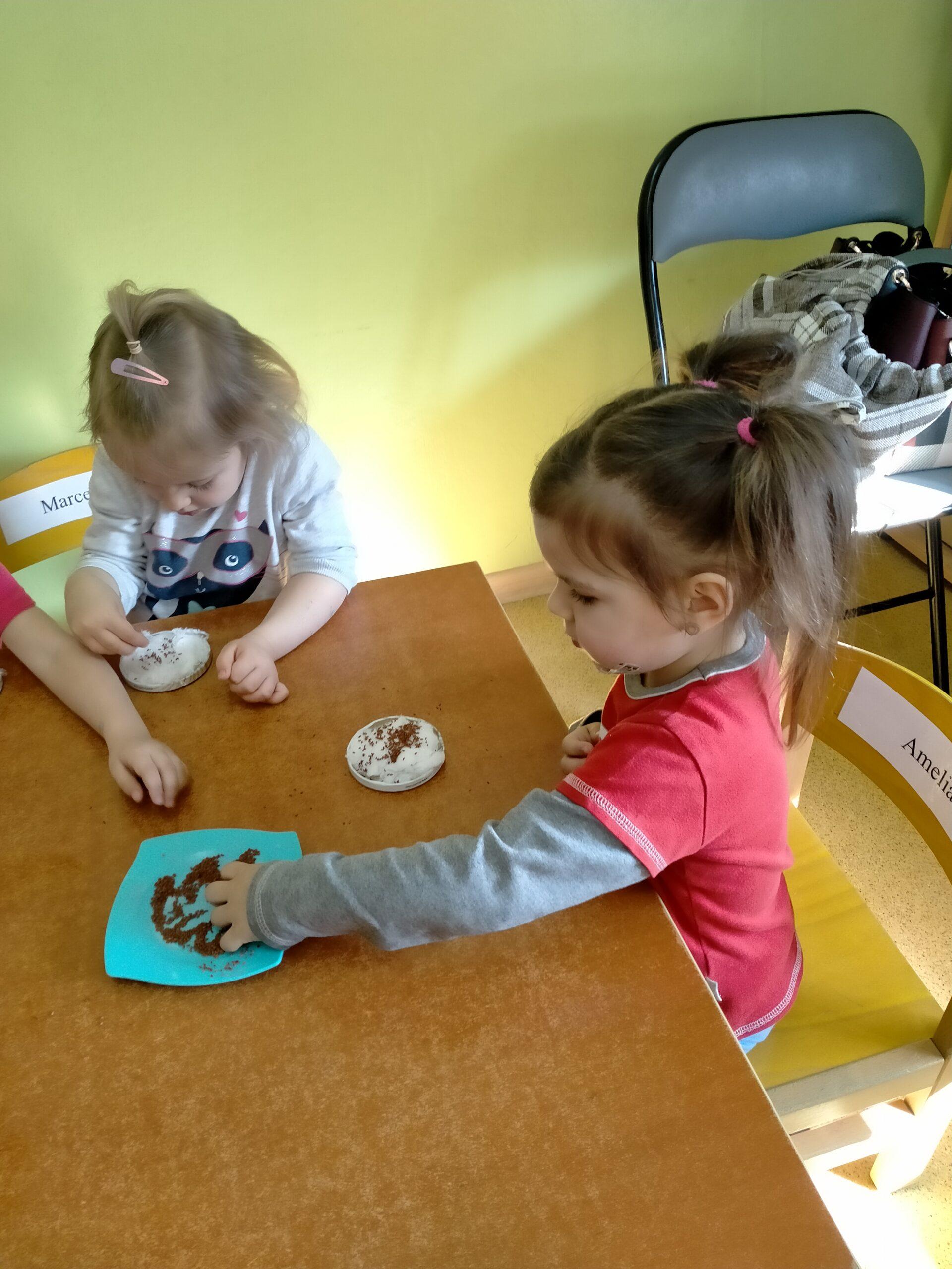 Dziewczynka bierze do rączki nasionka rzeżuchy.