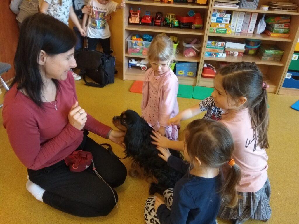 Właścicielka i dziewczynki siedzą na podłodze i głaszczą psa