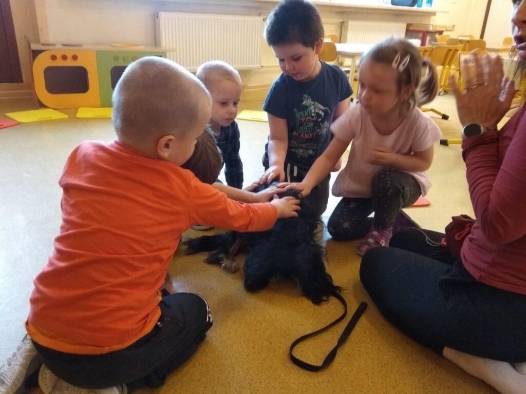 Chłopcy i dziewczynka głaszczą psa