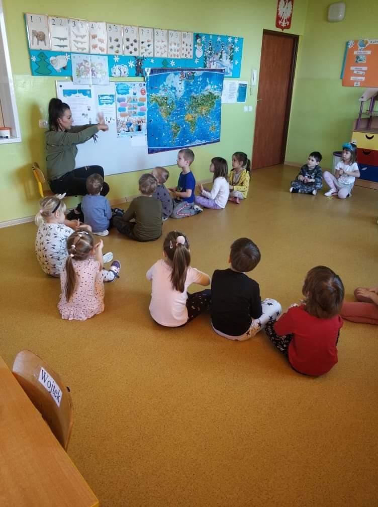 grupa dzieci siedzących na ziemi patrzy na panią