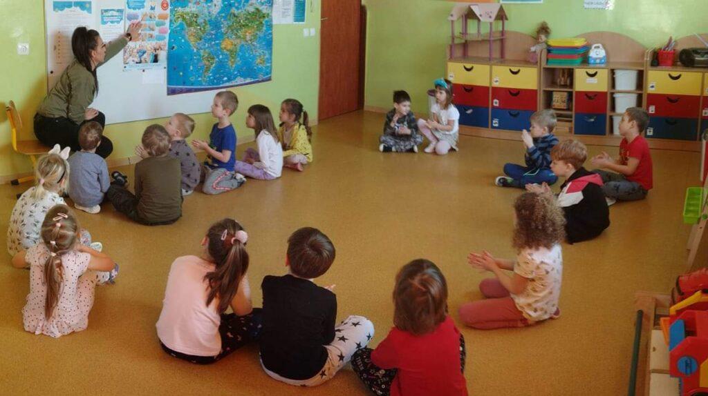 grupa dzieci siedzących na ziemi patrzy na tablicę i panią