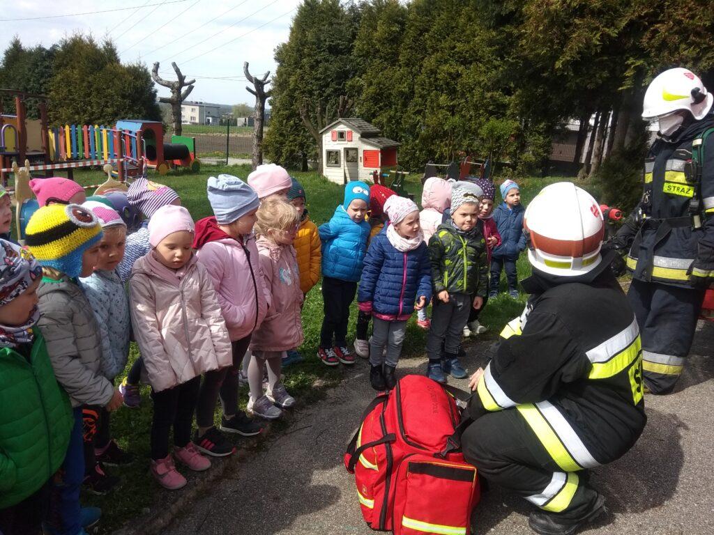 dzieci stoją obok siebie i patrzą na strażaków