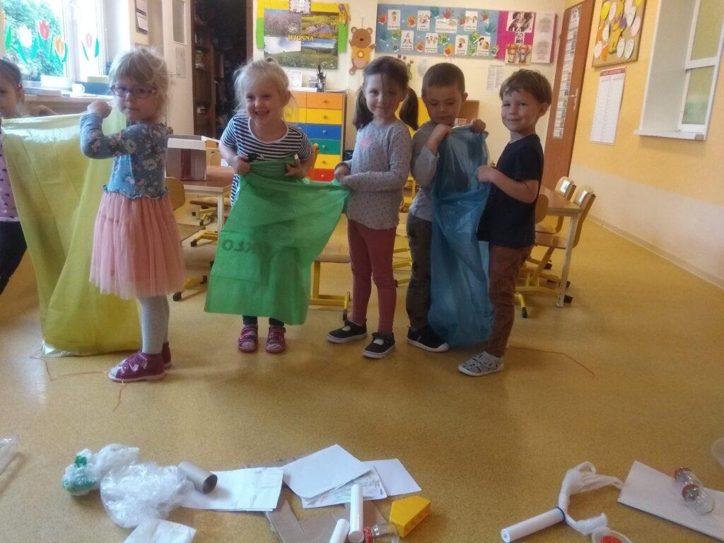 dzieci trzymają worki do segregacji śmieci, na podłodze leżą papierki, puszki, worki