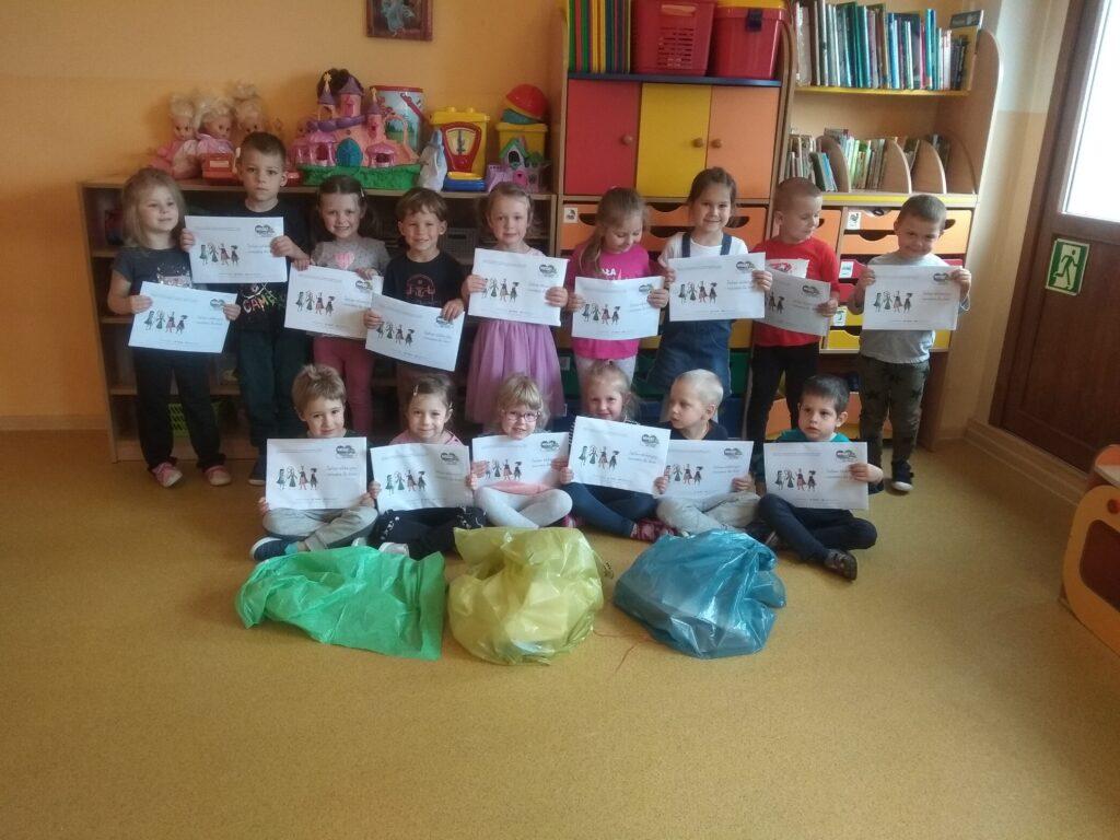 dzieci stoją i siedzą na podłodze, trzymają w rękach koperty z kartami pracy
