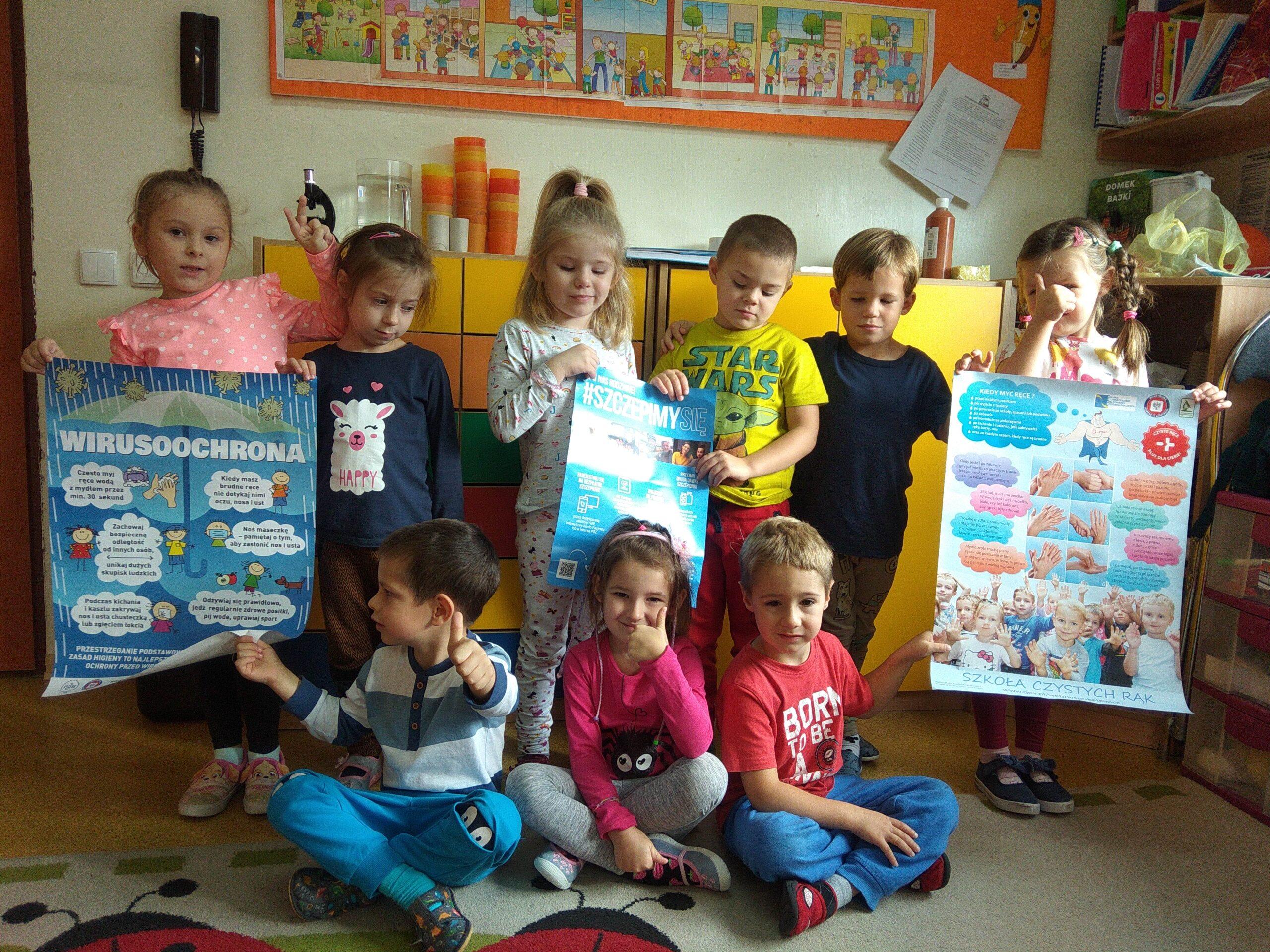 Grupa dzieci trzymają w rękach plakaty dotyczący ochrony przed wirusami
